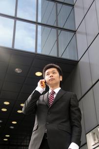 ビルを背に携帯電話で話す若いビジネスマンの素材 [FYI00118171]