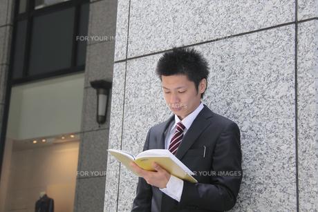 手帳を読む若いビジネスマンの写真素材 [FYI00118175]