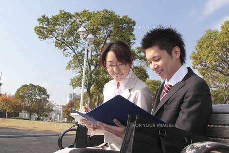 ベンチで資料を見る若いビジネスマンとビジネスウーマンの写真素材 [FYI00118176]