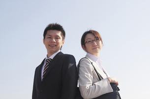 笑顔で背中合わせで立つ若いビジネスマンとビジネスウーマンの素材 [FYI00118177]