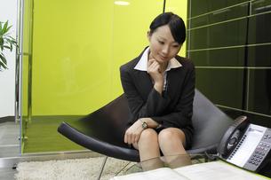 オフィスで書類を見つめる若いビジネスウーマンの素材 [FYI00118187]