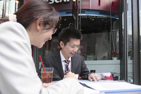 カフェで資料を見る若いビジネスマンとビジネスウーマンの写真素材 [FYI00118192]