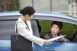 車内の上司に書類を渡す若い女性社員の素材 [FYI00118193]