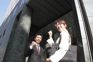 ビルの前で笑顔でガッツポーズをするビジネスマンとビジネスウーマンの素材 [FYI00118195]