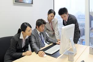 上司のパソコンをのぞき込む若い社員たちの素材 [FYI00118196]