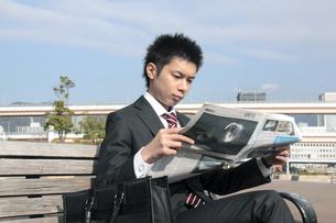 ベンチで新聞を読むビジネスマンの写真素材 [FYI00118197]