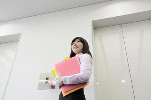 エレベーターを呼ぶ若い女性社員の素材 [FYI00118198]