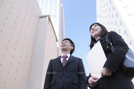 ビルの隙間から笑顔で上を見上げる若い会社員たちの素材 [FYI00118201]