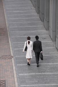 ビジネス街を歩くビジネスマンとビジネスウーマンの後ろ姿の素材 [FYI00118204]
