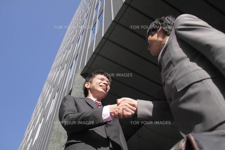 オフィス街で握手をするビジネスマンの素材 [FYI00118209]