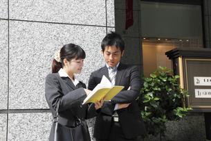 屋外で打合せをするビジネスマンとビジネスウーマンの素材 [FYI00118220]