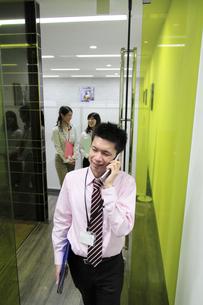 オフィス 携帯電話で話す若いビジネスマンの素材 [FYI00118230]