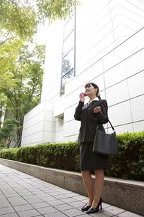 オフィス街で電話をする若い女性社員の素材 [FYI00118232]