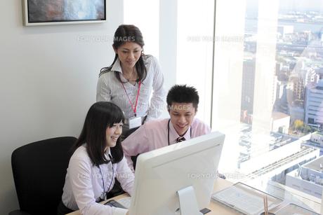 笑顔でパソコンを覗くビジネスマンたちの素材 [FYI00118242]