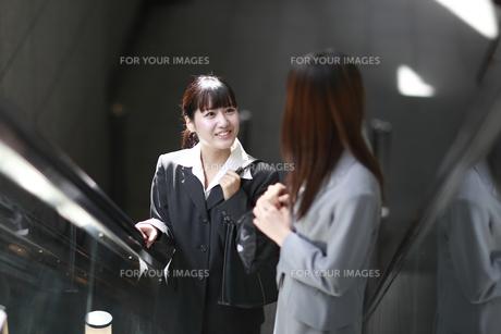 エスカレーターで話す若いビジネスウーマンの写真素材 [FYI00118246]