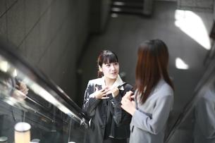 エスカレーターで話す若い女性の素材 [FYI00118251]