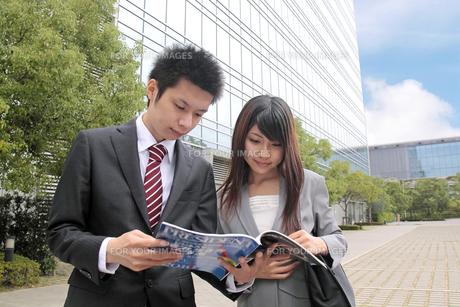 屋外で雑誌を読む若いビジネスマンたちの素材 [FYI00118256]