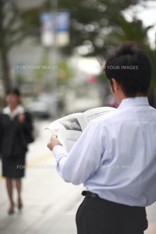 新聞を読むビジネスマンの後ろ姿の素材 [FYI00118268]