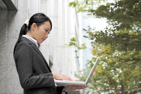 屋外でノートパソコンを開く若い女性の素材 [FYI00118299]