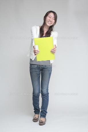 両手で黄色いファイルをもつ女性の素材 [FYI00118372]