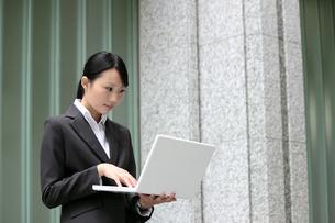 ビジネス パソコンを手に持つビジネスウーマンの素材 [FYI00118422]