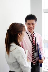 オフィス 笑顔で会話する男女の写真素材 [FYI00118427]