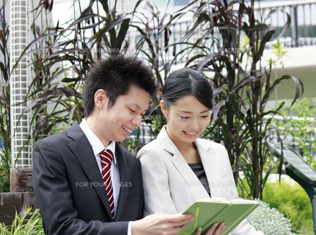 ビジネス 手帳を見つめる男女の素材 [FYI00118434]