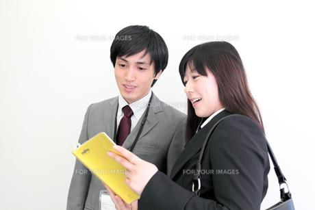 オフィス 手帳を見つめ会話する男女の素材 [FYI00118439]