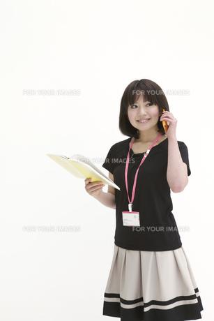 手帳を手に電話をするビジネスウーマンの写真素材 [FYI00118455]