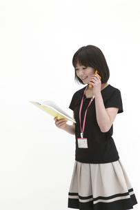 手帳を確認しながら電話するビジネスウーマンの写真素材 [FYI00118456]