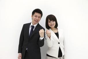 並んでガッツポーズをするビジネスマンとビジネスウーマンの写真素材 [FYI00118473]