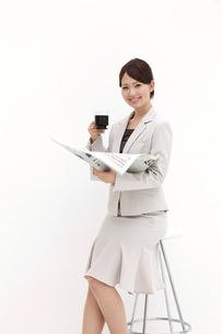 腰を掛け新聞を手にするビジネスウーマンの写真素材 [FYI00118495]