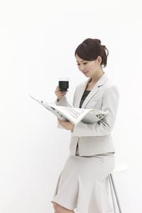 熱心に新聞を読むビジネスウーマンの素材 [FYI00118497]