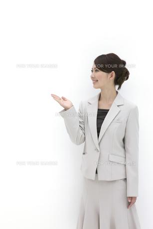 右手を挙げ案内をするビジネスウーマンの素材 [FYI00118504]