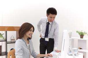パソコンを見つめ会話するビジネスマンとビジネスウーマンの写真素材 [FYI00118505]