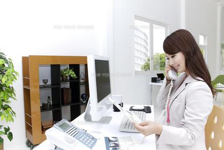書類を手に電話をするビジネスウーマンの写真素材 [FYI00118506]