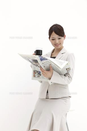 新聞を読み微笑むビジネスウーマンの素材 [FYI00118516]