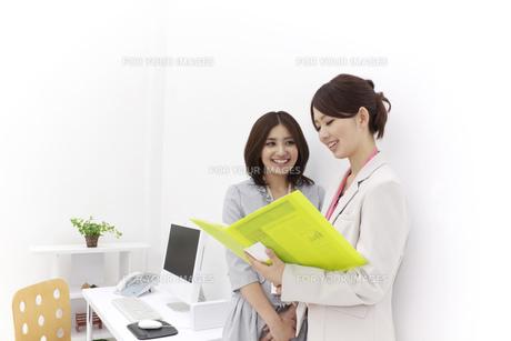 笑顔で会話するビジネスウーマン2人の素材 [FYI00118522]