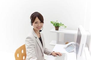 インカムをつけパソコンを操作するビジネスウーマンの素材 [FYI00118530]