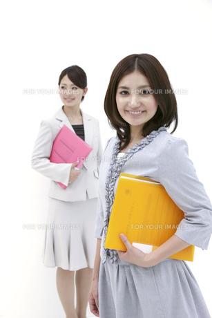 ファイルを抱え笑顔のビジネスウーマン2人の素材 [FYI00118537]
