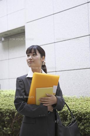 オレンジ色のファイルを抱え遠くを見つめるビジネスウーマンの素材 [FYI00119151]