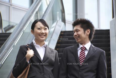 エスカレーターを降りるビジネスマンとビジネスウーマンの素材 [FYI00119154]