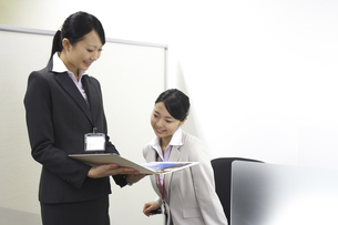 同僚に資料を見せるビジネスウーマンの素材 [FYI00119158]