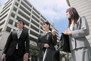 並んでオフィス街を歩くビジネスマンとビジネスウーマンの写真素材 [FYI00119160]