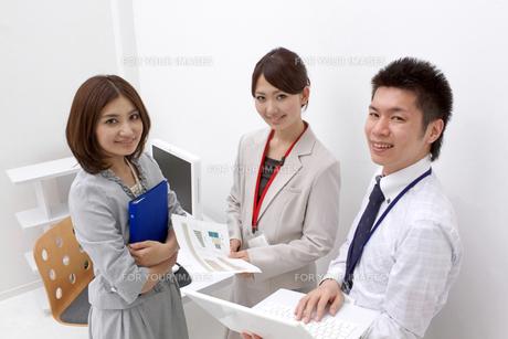 パソコンを手にミーティングをするビジネスマンとビジネスウーマンの素材 [FYI00119162]
