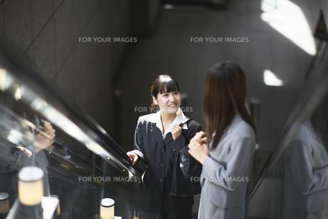 エスカレーターで話す若いビジネスウーマン2人の写真素材 [FYI00119168]