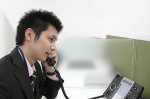 オフィス 電話で話す若いビジネスマンの写真素材 [FYI00119171]