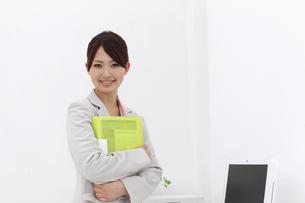 オフィス ファイルを抱える笑顔のビジネスウーマンの素材 [FYI00119172]