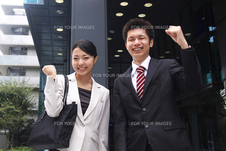 ビルの前でガッツポーズをするビジネスマンとビジネスウーマンの素材 [FYI00119173]