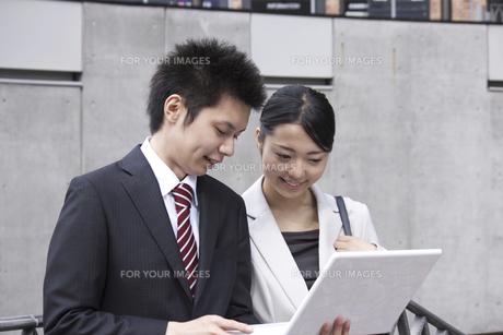 屋外でノートパソコンを使い説明するビジネスマンの素材 [FYI00119177]